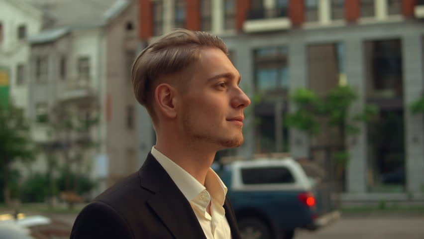 Side view profile successful young businessman walk down the street, caucasian man walking along the road outdoors. on background cars are passing by | Shutterstock HD Video #1012093592