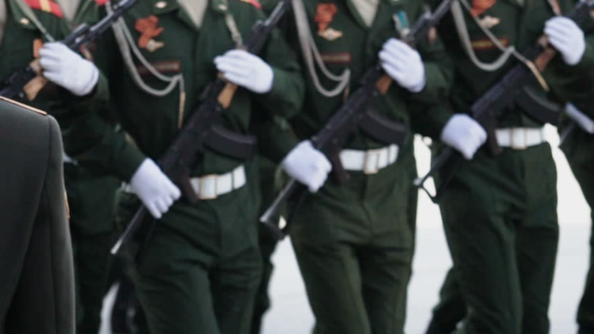 A close-up of the going military at the parade of holding AK-47 assault rifles. A close-up of the marching military with a submachine gun in his hand slow motion.