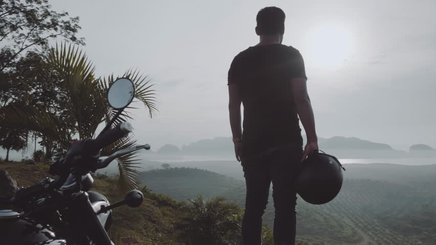 Back view of cool traveler standing in front of his chopper motorbike and admiring beautiful tropical mountain view during cloudy early morning - video in slow motion | Shutterstock HD Video #1012097330