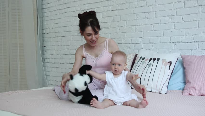 Happy young mother and her girl with play on bed with toy Panda bear home smiling.
