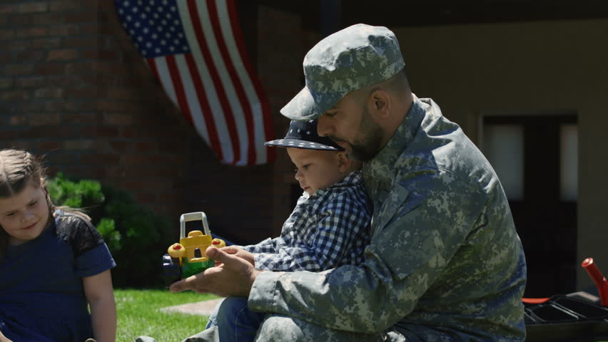 Adult man wearing military uniform embracing daughter and relaxing in summer garden before leaving to army in backyard
