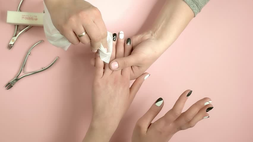 Manicurist wiping manicured fingers to client. The process of cleaning of female manicured hands by beautician in nail salon, top view. Manicure finishing concept. Royalty-Free Stock Footage #1012113098