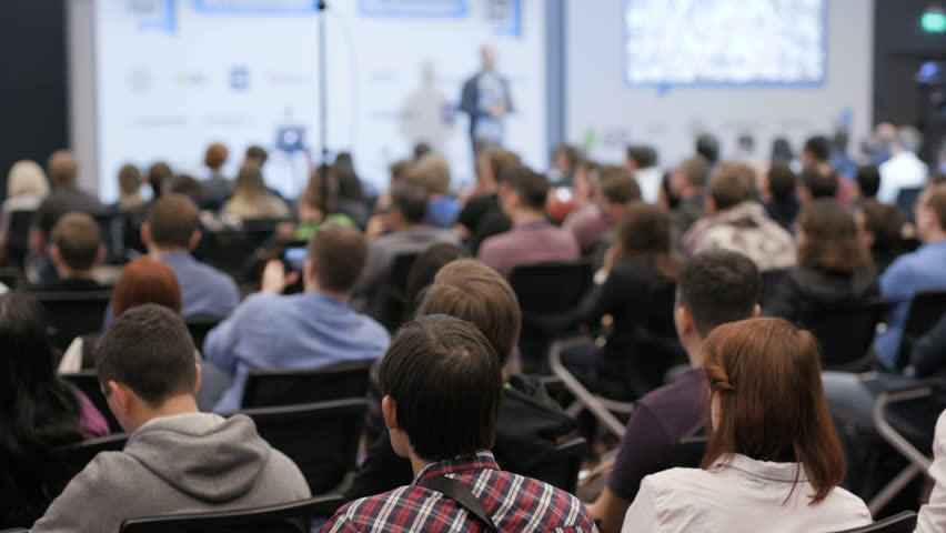 Modern space for startup company of programmers career. Commerce activity for cooperation or success in large crowded room. Speaker says about successful marketing in full place of viewers slow motion Royalty-Free Stock Footage #1012115246