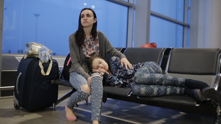 A woman with her daughter at the airport in the waiting room, spend the night and wait for flight