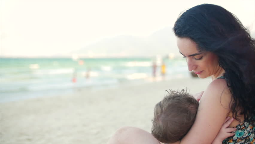 Mom with baby are enjoying fresh air sit by the sea, mom is breastfeeding the baby and lulling him.