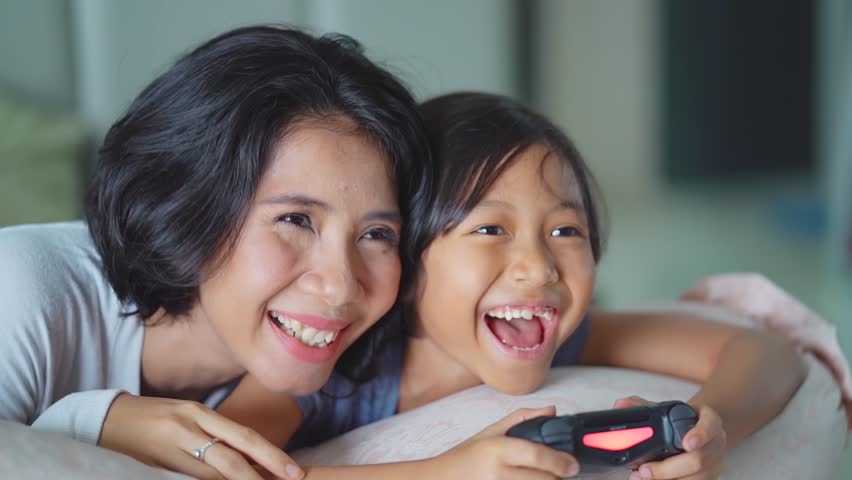 JAKARTA, Indonesia - June 05, 2018: Cheerful little girl and her mother playing video game in the bedroom at home. #1012147310