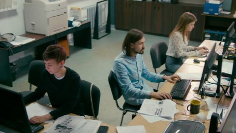 Young Employees are Working in the Open Space Office at Common Desk with Computers