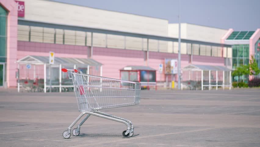 Pushing an empty shopping cart at parking. Shopping trolley in a parking lot near a supermarket.