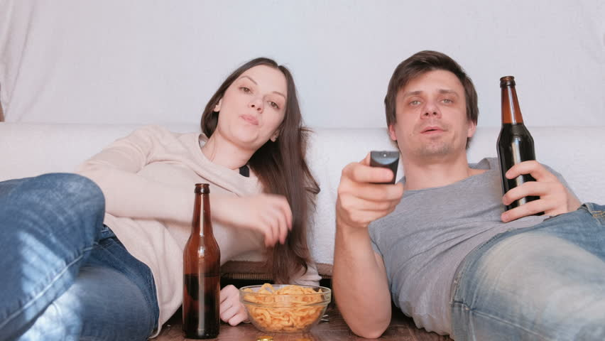 Couple of young man and woman eating chips drinking beer and watching TV, switching channel. Talking and smiling