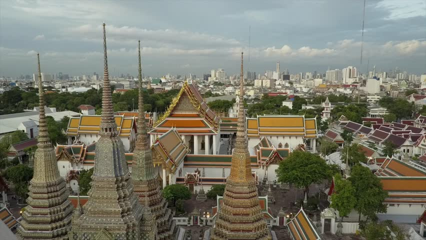 Wat Phra Kaew temple in Bangkok beautiful drone view in 4K. Aerial shot of amazing Thai Buddhist temple. Unique perspective close over golden roof and skyline background. Wat Pho | Shutterstock HD Video #1012161656