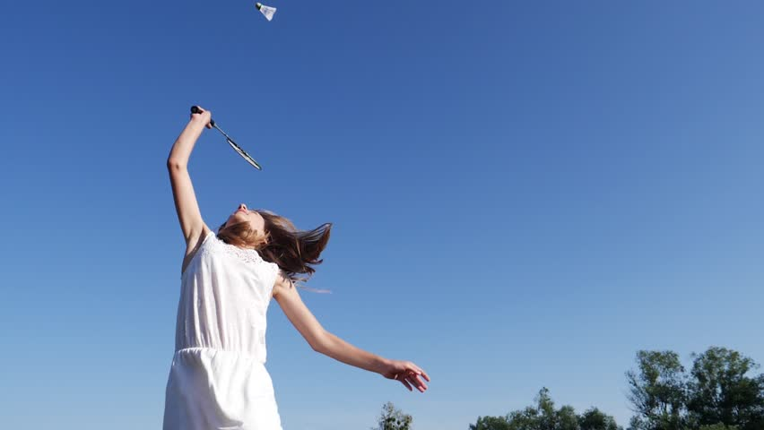 Teenager young girl on summer countryside jump hit the shuttlecock playing badminton