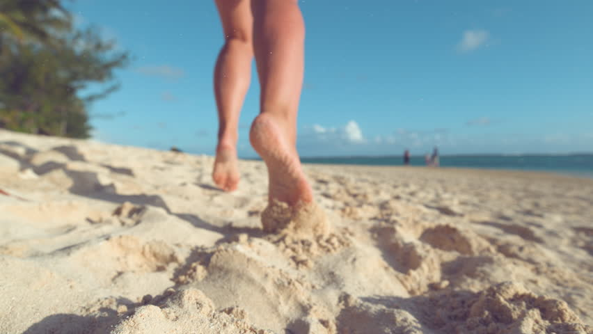 SLOW MOTION, CLOSE UP, LOW ANGLE, DOF: Particles of sand fly in the air as unrecognizable woman jogs barefoot on the tropical beach on remote island. Cheerful girl runs along ocean in the summer sun. #1012187810