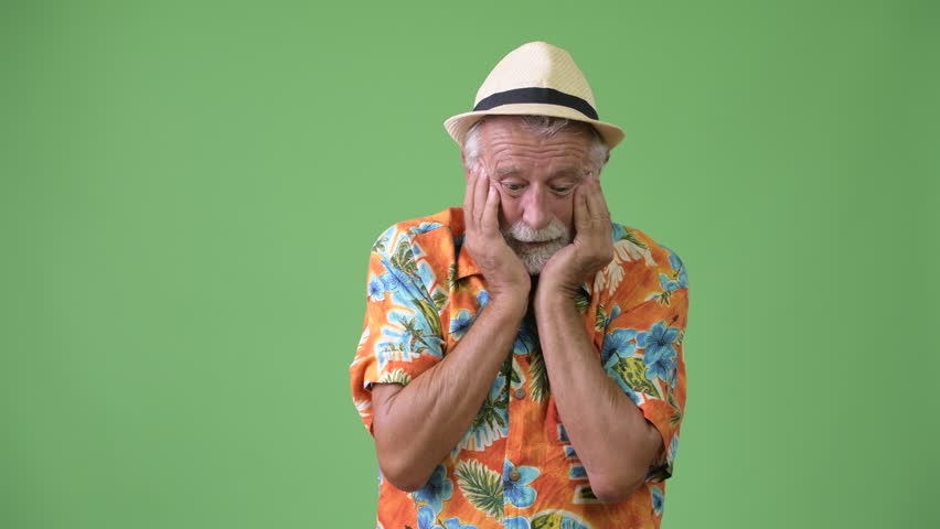 Handsome senior bearded tourist man ready for vacation against green background | Shutterstock HD Video #1012195364