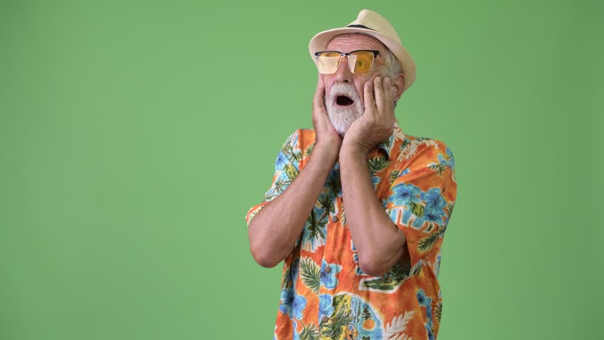 Handsome senior bearded tourist man ready for vacation against green background | Shutterstock HD Video #1012195376