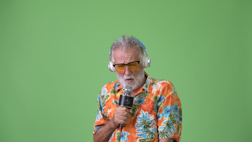 Handsome senior bearded tourist man ready for vacation against green background | Shutterstock HD Video #1012195385