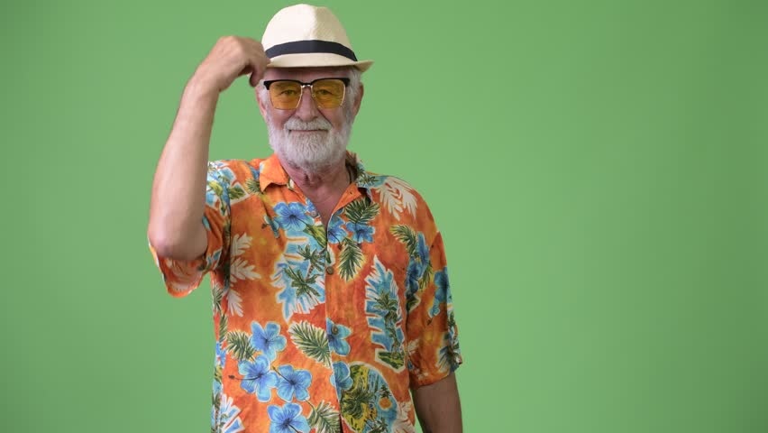 Handsome senior bearded tourist man ready for vacation against green background | Shutterstock HD Video #1012195394