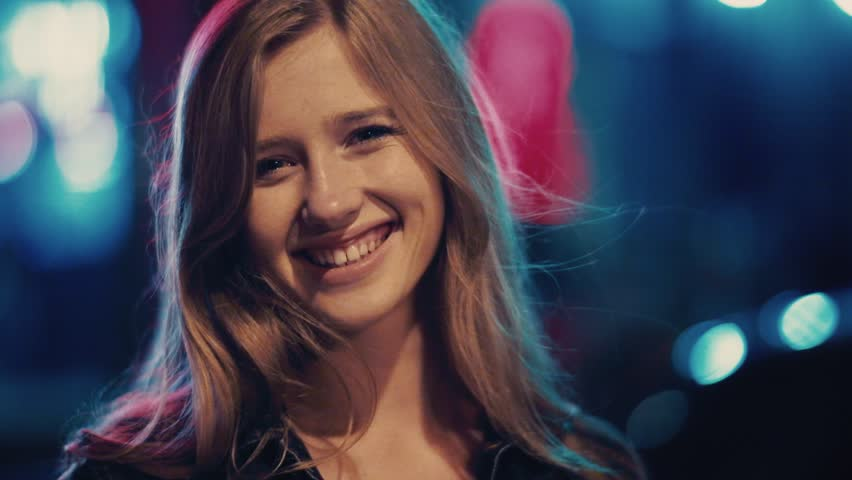 Close up view of gorgeous young woman adjusting her hair, looking straight to camera and smiling happily. Cheerful mood, positive emotions, self-confidence. City lights background. Female portrait | Shutterstock HD Video #1012197944