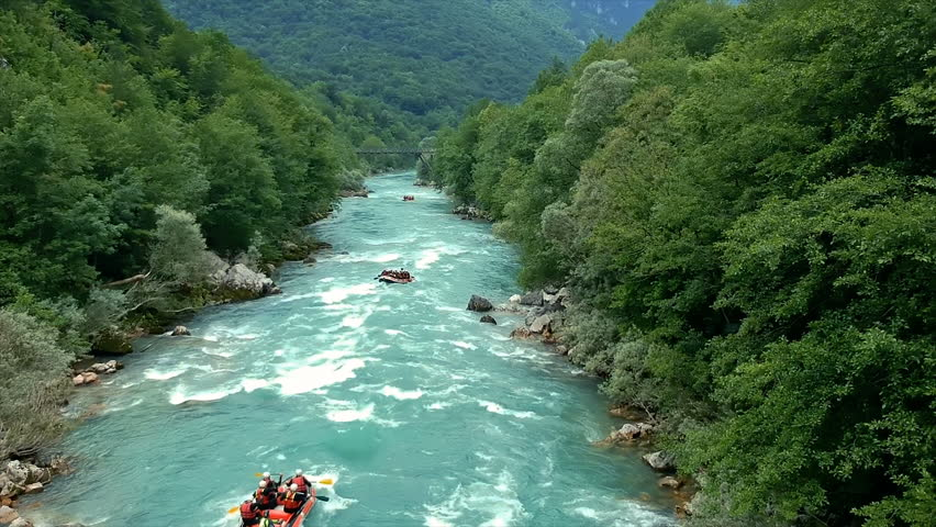 Aerial shot of people white water rafting on Rouge River. Whitewater rafting teams descending raging rapids with paddles splashing in water. Three rafting boats on whitewater.