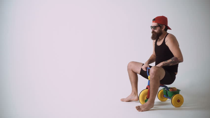 A funny bearded man is riding a children's bicycle.