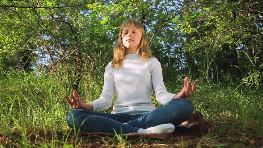 Teenage girl meditating practicing yoga at sunset in the forest   Shutterstock HD Video #1012210169