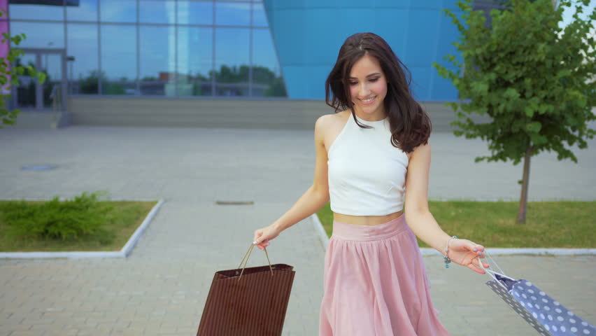 Active attractive girl dances near a shopping center with full of purchases shopping bags #1012210373