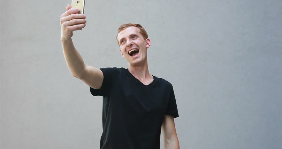 Fashion, style, emotions and people concept - Close up portrait of a redhead of a beautiful manly guy with freckles. Selfie time, blogger is making photo for her social networks page. | Shutterstock HD Video #1012225358