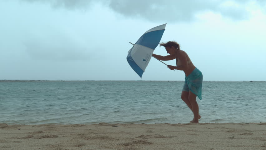 Woman's umbrella gets broken by the strong monsoon wind while she walks down the sandy tropical beach. Young female traveler gets caught in horribly windy weather during her trip to the seaside.