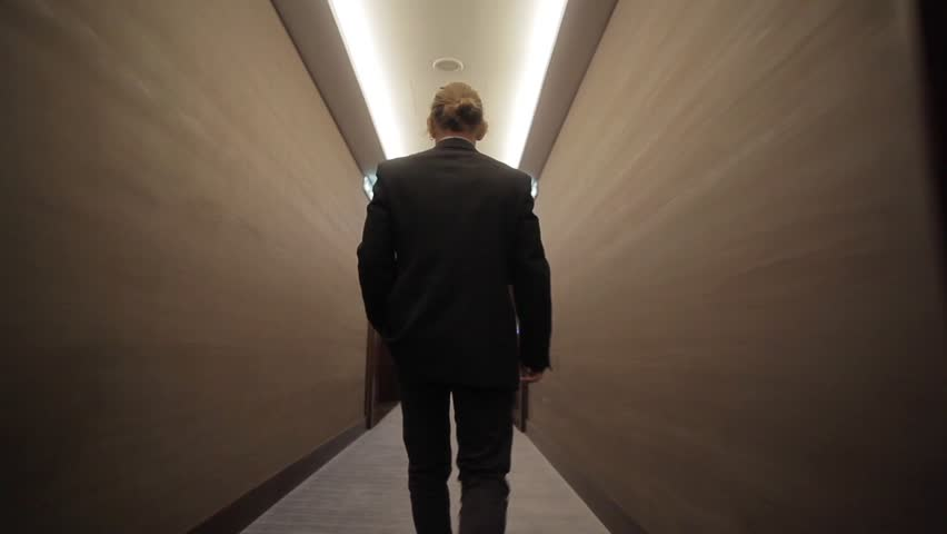Young businessman going along long narrow corridor with closed doors back view pov camera sliding. Man in business suit clothing walks room hall to meeting work indoors. Office style building success   Shutterstock HD Video #1012244786