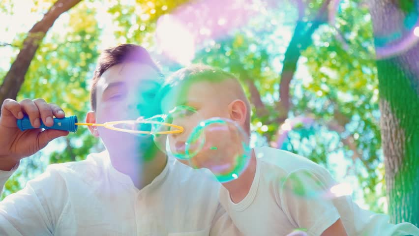 Father with his son blowing soap bubbles, fun family pastime, a child having fun with his dad | Shutterstock HD Video #1012260239