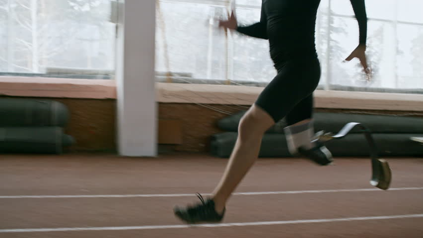 Tracking shot with tilt up of disabled sportsman with artificial fitness leg sprinting on indoor track