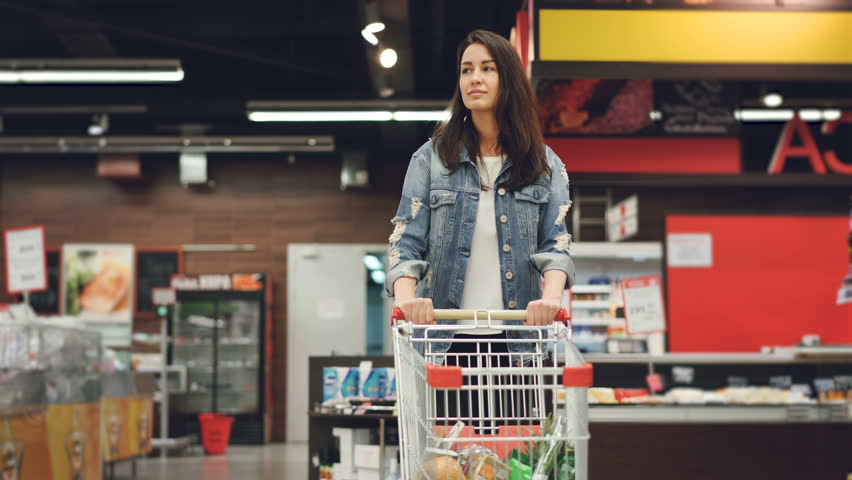 Pretty lady in casual clothes is walking in grocery store steering shopping trolley with food inside it and looking around at shelves with products. Women and shops concept.