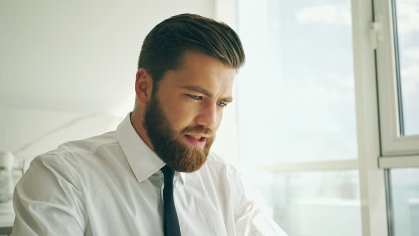 Smiling bearded business man sitting by the table on kitchen while drinking coffee and using laptop computer | Shutterstock HD Video #1012264595