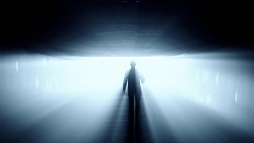 Silhouette of person walking in tunnel to the bright light.