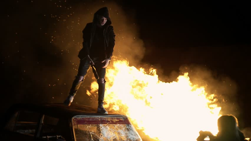 Revolution destructive behavior guy on the car with a baseball bat breaks glass. In the background is a fire. shooting at night