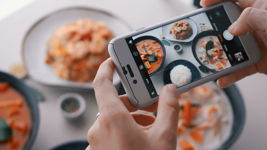 Female hands take photos of food by modern smartphone. Closeup. 4K.