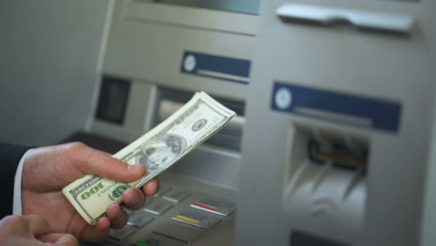 Man counting dollars withdrawn from ATM, putting cash in wallet, 24h service