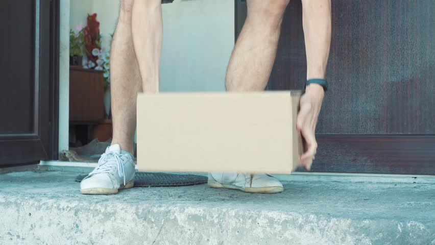 A man picks up a package from outside his front door #1012307339