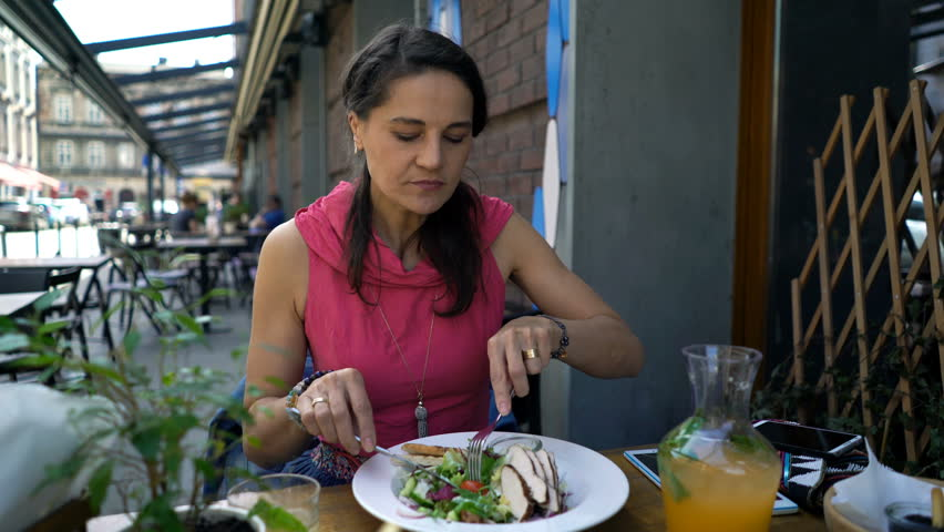 Beautiful young woman eating distasteful, awful salad for lunch in cafe