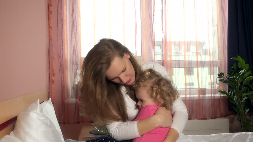 Mother calm down her little worried child girl by hugging embracing in bed. Handheld steadycam flycam movement shot. 4K UHD #1012315364