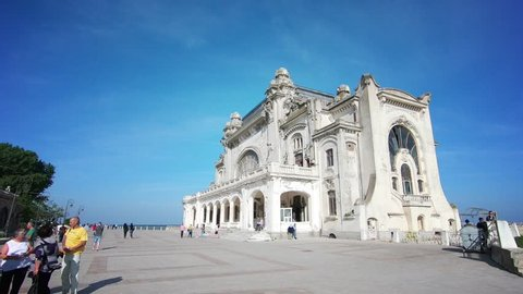 Constanta, Romania - June 10, 2018: Footage of the abandoned casino in Constanta, Romania, with people walking by.