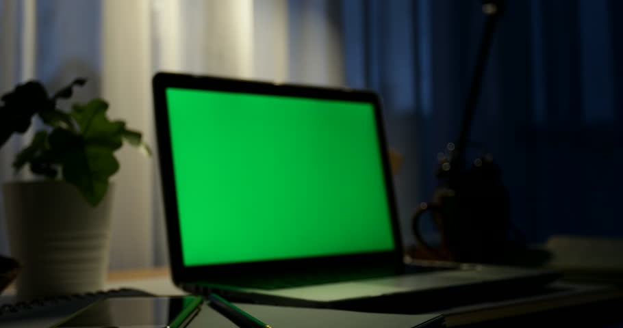 Laptop with green screen. Dark office. Dolly in and out. Perfect to put your own image or video.Green screen of technology being used. Chroma Key laptop | Shutterstock HD Video #1012335218