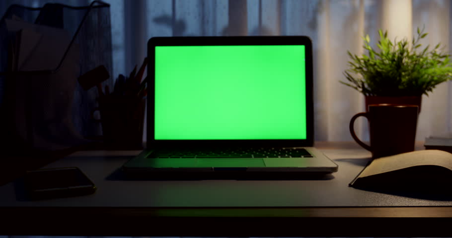 Laptop with green screen. Dark office. Dolly in. Perfect to put your own image or video.Green screen of technology being used. Chroma Key laptop | Shutterstock HD Video #1012335224