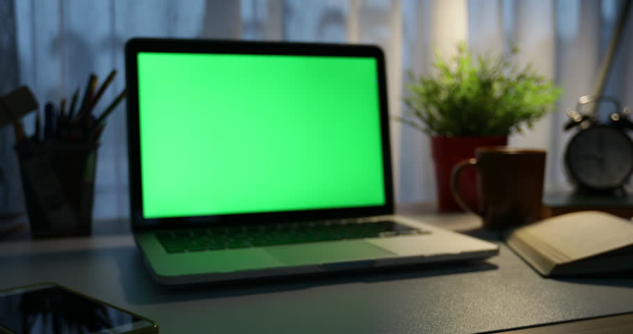 Laptop with green screen. Dark office. Dolly in . Perfect to put your own image or video.Green screen of technology being used. Chroma Key laptop #1012335227