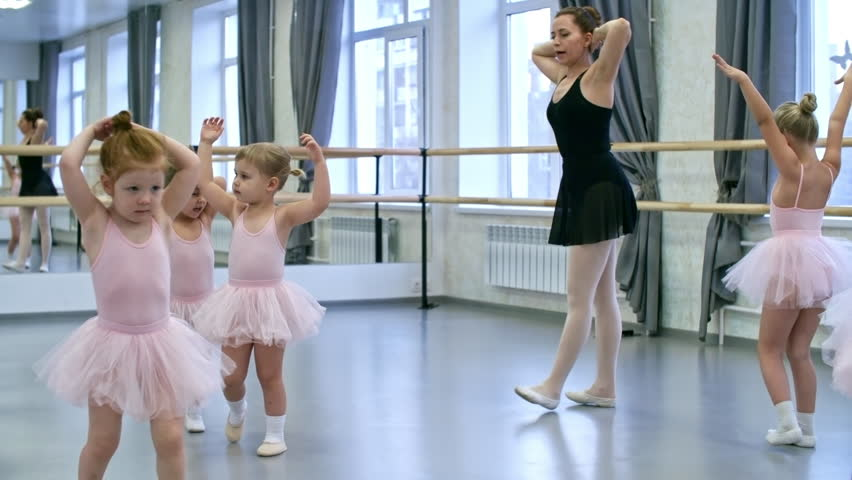 Group of six primary school girls in tutu skirts and leotards walking in circle when doing warm up exercises, their teacher correcting them | Shutterstock HD Video #1012343258