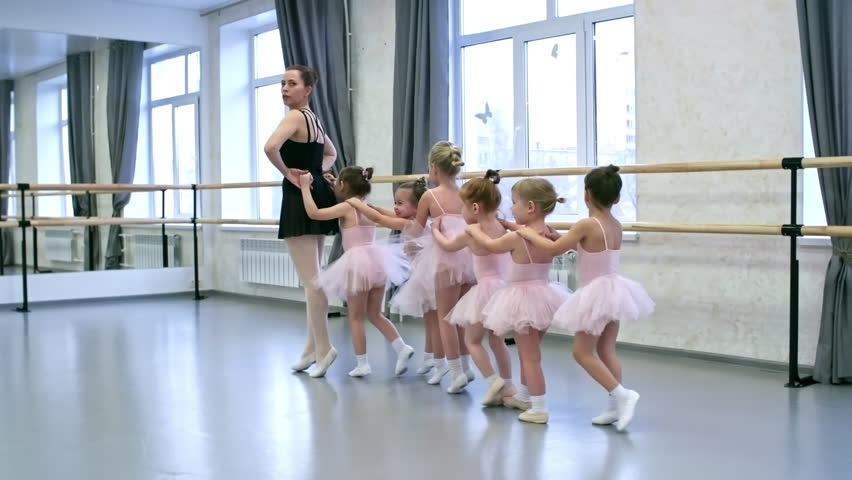 Group of little girls and their female teacher walking on tiptoes one behind the other and learning new dance moves during ballet lesson | Shutterstock HD Video #1012343399