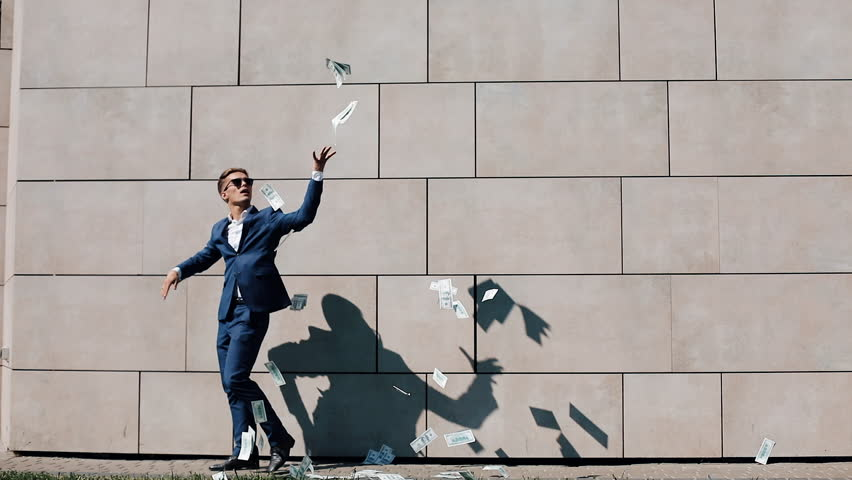 Young happy businessman scatter the dollars and funny dancing in the street. Money rain, falling dollars. It is located near the office center, slow motion. Successful business. Shot on Red Epic | Shutterstock HD Video #1012344794
