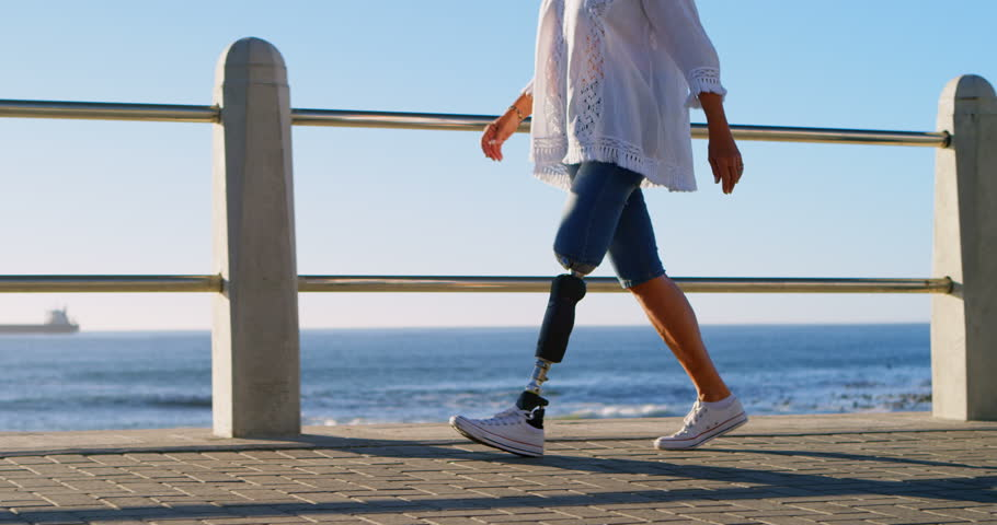 Midsection of disabled woman walking near beach on a sunny day 4k