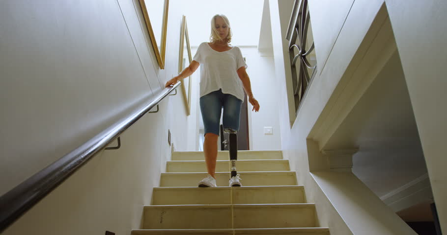 Disabled woman with prosthetic leg moving downstairs at home 4k