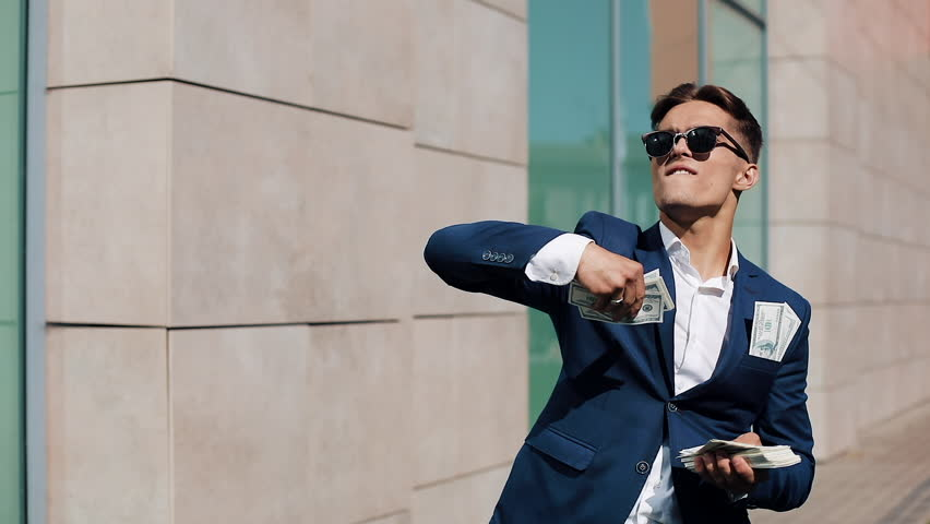 Young happy businessman scatter the dollars and funny dancing in the street. Money rain, falling dollars. It is located near the office center, slow motion. Successful business. Shot on Red Epic | Shutterstock HD Video #1012346249