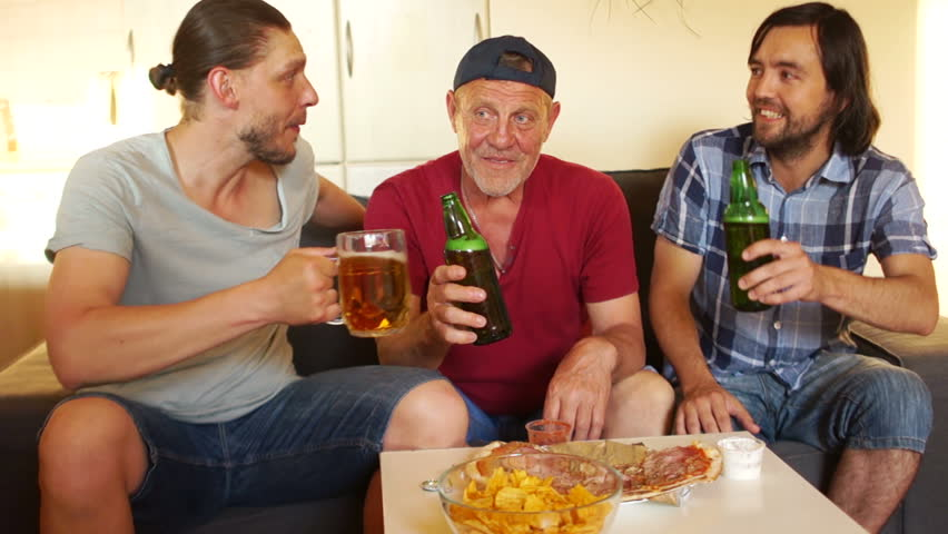 Two grown sons drink beer with their father. Family weekend. Football fans. Men are talking lively and laughing cheerfully #1012347941